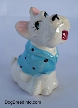 A Scottish Terrier figurine sitting with a blue with black dots shirt on. The figurine has cartoon features.