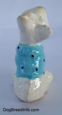 The back of a white ceramic Scottish Terrier that is sitting with a blue with black shirt on figurine. The figurine has a short tail on its back.