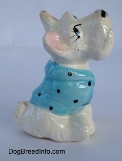 The right side of a white ceramic Scottish Terrier sitting and it has a blue with black shirt on figurine. The figurine has small perky ears.
