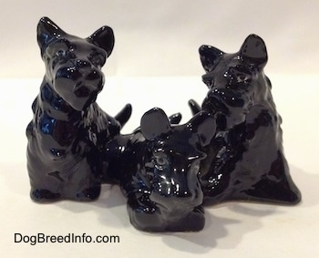 A black Scottish Terrier figurine trio. The figurines are not painted.