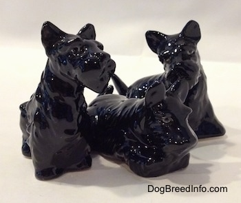 The front right side of a figurine of a black Scottish Terrier trio. The figurines are glossy.
