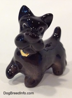 The front left side of a black figurine of a Scottish Terrier walking. The figurine has its front right paw in the air.