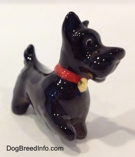 The front right side of a black figurine of a Scottish Terrier. The figurine has black circles for eyes.