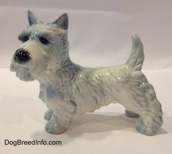 The left side of a white Scottish Terrier figurine with blue highlights. The figurine has short legs.