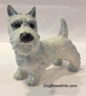The front left side of a white with blue highlights Scottish Terrier figurine. The figurine has its ears in the air.