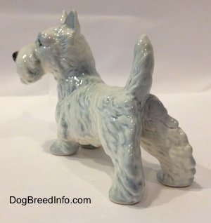 The back left side of a figurine of a white with blue Scottish Terrier. The figurines body is longer than its legs.