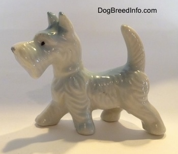 The left side of a bone china white Scottish Terrier figurine. The figurine has short legs.
