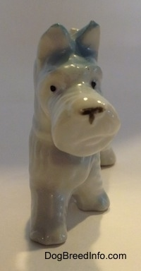 A white bone china Scottish Terrier figurine with blue ears. The figurine has small black circles for eyes.
