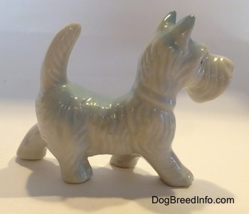 The right side of a white bone china figurine of a Scottish Terrier. The figurine has hair details along its head and back.