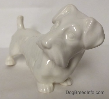 The front right side of a white unpainted Sealyhan Terrier figurine. It is hard to see the features of the figurine.