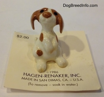 A figurine of a white and brown Mini Curbstone Setter puppy that is in a begging pose.