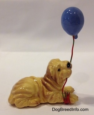 The right side of a Shar-Pei lying figurine with a blue balloon in its mouth.