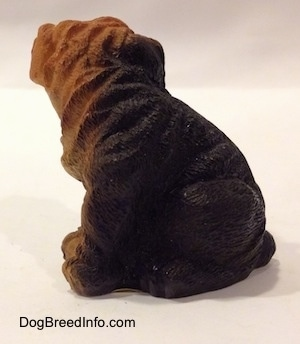 The left side of a black with brown figurine of a Shar-Pei puppy in a sitting position. The figurine has wrinkle details along its body.