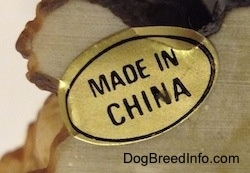 Close up - On the underside of a figurine of a Shar-Pei puppy is the a gold sticker that reads 'Made in China'.