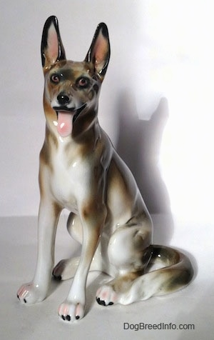 A figurine of a brown and white with black German Shepherd sitting. The figurine has its ears in the air.