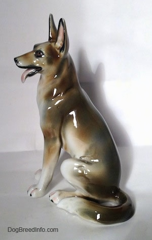 The left side of a figurine of a brown and white with black sitting German Shepherd. The figurine has a long tail that is layed to the left side of the figurine.