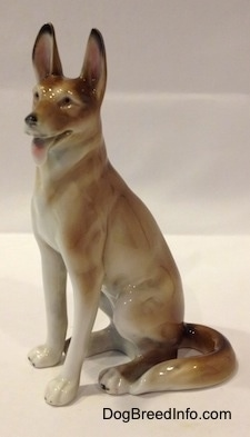 The left side of a brown and white German Shepherd sitting figurine. The figurine has its long tail wrapped around its left side.