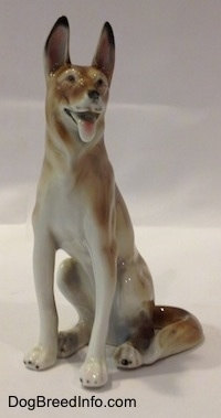 The front left side of a sitting brown with white German Shepherd figurine. The figurine has its tongue out and black circles for eyes.