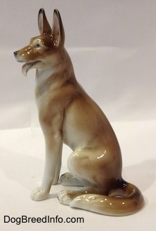 The side of a brown and white figurine of a German Shepherd sitting.