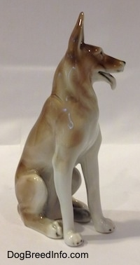 The front right side of a white and brown figurine of a German Shepherd sitting. The figurine has long white legs with black tipped nails.