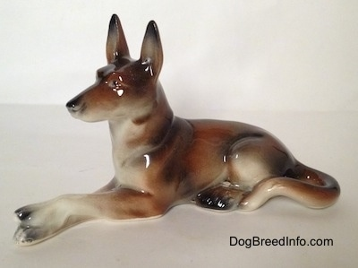 The left side of a brown and white with black German Shepherd figurine lying. The figurine is glossy.