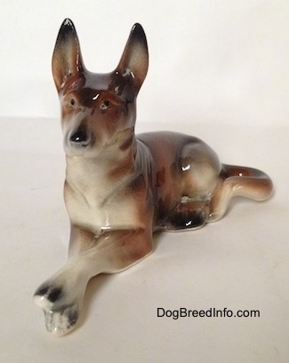 The front left side of a brown and white with black figurine of a German Shepherd lying figurine. The figurine has tiny black circles for eyes.