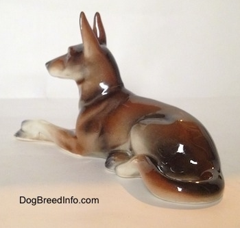 The back left side of a figurine of a brown and white with black German Shepherd lying figurine. The figuirine has its long white legs sticking out and it has black tipped nails.