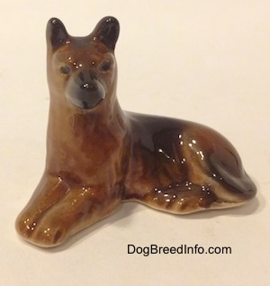 The front left side of a brown with black Shepherd figurine in a lying pose. The figurine has small black circles for eyes.