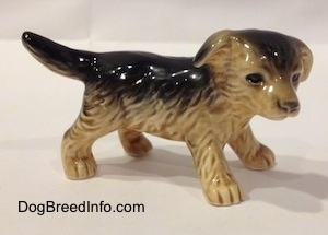 The right side of a black with tan figurine of a German Shepherd puppy. The figurine has fine hair details.