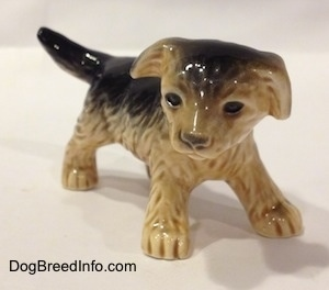 The front right side of a figurine of a black with tan German Shepherd puppy. The figurine has black circles for eyes and the eyes have a gloss to them.