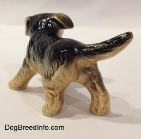The back left side of a black with tan German Shepherd puppy figurine. The figurine has a tail that is the length of its body.