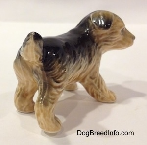 The back right side of a figurine of a black with tan German Shepherd puppy standing. The figurines ears are black tipped and flopped over.