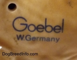 Close up - The underside of a figurine of a German Shepherd puppy. It has the stamp of Goebel W.Germany on it.