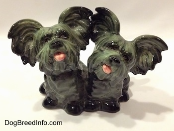 The front of a Siamese twin Skye Terrier figurine. The figurines tongues are out.