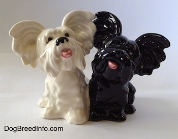 A figurine of a black Skye Terrier and a white Skye Terrier. The figurines mouths are painted open and they are looking up.