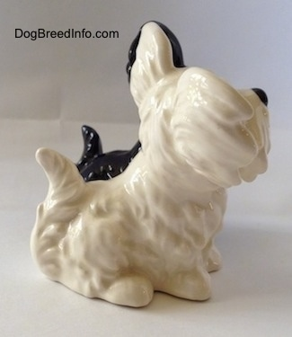 The right side of a figurine two of Skye Terriers sitting. The figurines have fine hair details.