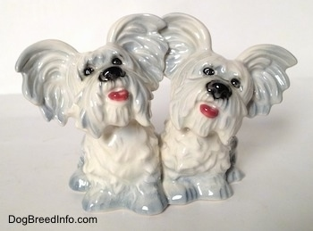 A figurine of Siamese silver platinum Skye Terrier twin figurines. The figurines mouths are painted open.