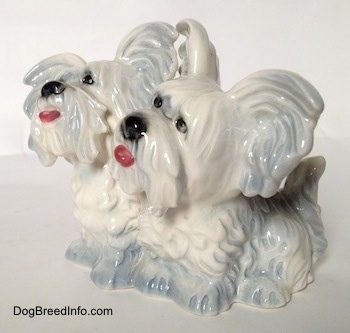 The front left side of a silver platinum figurine of a Siamese twin Skye Terrier sitting. The figurines have short legs.