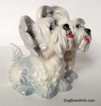 The front right side of a Siamese twin silver platinum figurine of a sitting Skye Terrier. The figurines have black circles for eyes.