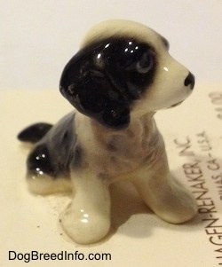 The front right side of a figurine of a black with white English Sprigner Spaniel puppy in a sitting pose. The ears of the figurine are hard to differentiate from its head.