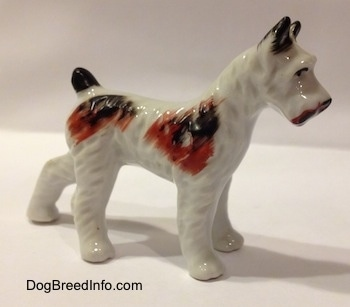 The front right side of a white with brown and black porcelain figurine of a Standard Schnauzer. The figurine has short ears.