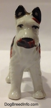 A porcelain white with brown and black Standard Schnauzer figurine. The figurine has black circles for eyes and brown around its mouth.