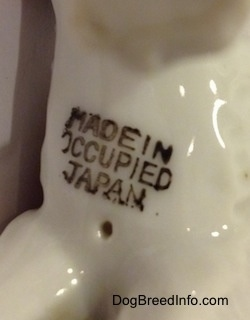 Close up - The underside of a porcelain figurine of a Standard Schnauzer figurine. The figurine has a stamp that reads 'Made in Occupied Japan'.