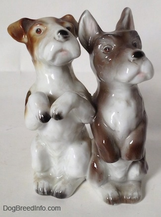 A figurine of two Jack Russell Terriers in a begging pose. They both are looking up and to the right.