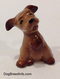 A brown Terrier puppy figurine in a sitting pose. The figurines ears are lifted up and its head is tilted to the left.