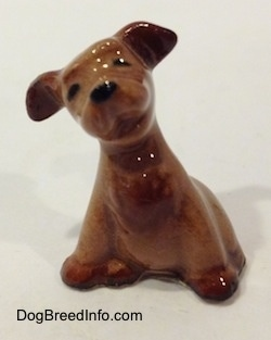 The front left side of a figurine of a brown Terrier puppy in a sitting pose. The figurine has black circles for eyes and a nose.