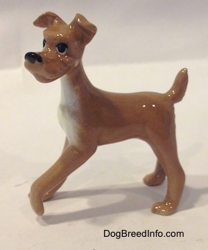 A tan with white figurine of a dog. The figurine has long legs.