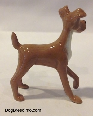 The right side of a tan with white figurine of a dog. The figurine has a medium length body.