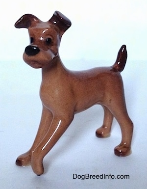 A brown with black figurine of a dog that looks like 'Tramp' from     Disneys The Lady and The Trump'.