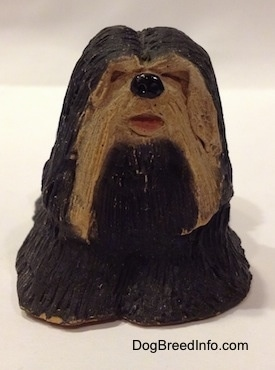 A black with tan figurine of a standing Tibetan Terrier. Its mouth is painted open.